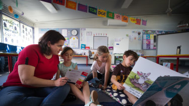 Mum and teacher Sarah Asome reading with her children Pippa, Harriet and Ned.