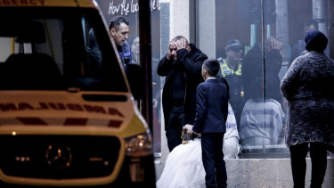A woman in a bridal gown and a young boy outside the venue.