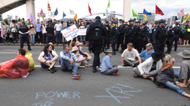 Activists glued themselves to the bridge and refused to leave after police issued a move-on order.