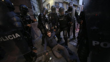 A man is detained by police blocking protesters from advancing closer to the presidential palace in Quito, Ecuador, last week.