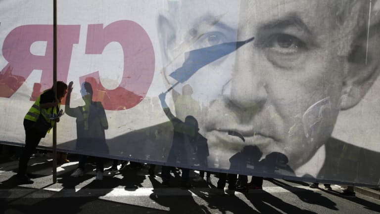Israelis demonstrate in Tel Aviv next to a banner showing Prime Minister Benjamin Netanyahu during a protest against the rising cost of living.