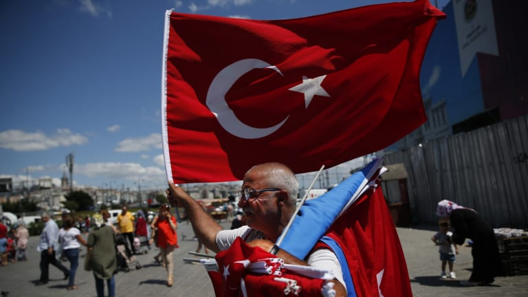 A vendor offers Turkish flags for sale at a market in Istanbul on Monday.