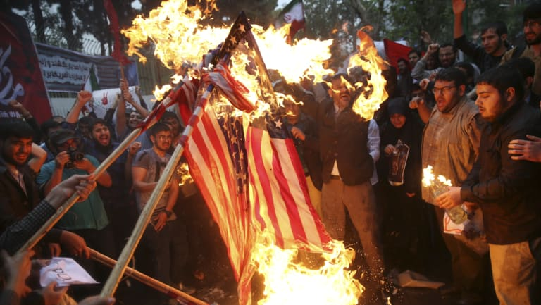 Hardline Iranian demonstrators burn US flags during a gathering in front of the former US Embassy in Tehran.
