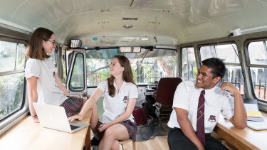 Tempe High School Year 12 students, Ursula Reynolds, Bella Lengyelfalusy and Raiyaan Ruhi, in a bus which has been converted into a hangout space.