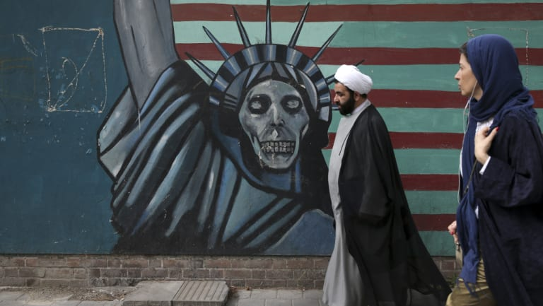 A cleric and a woman walk past an anti-US mural painted on the wall of the former American Embassy in Tehran.