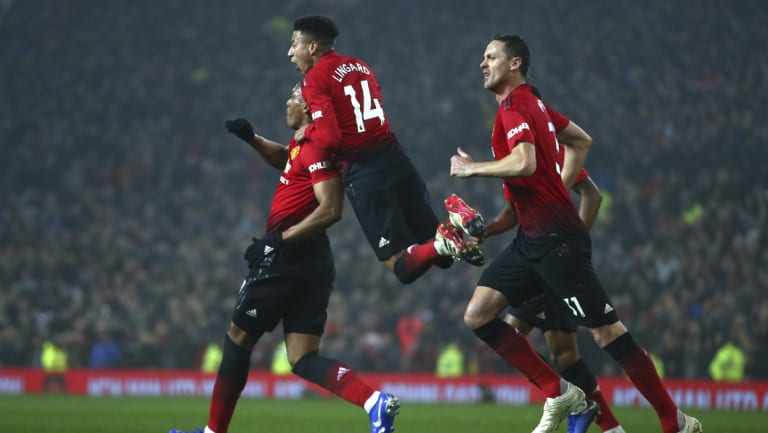 Manchester United's Jesse Lingard jumps on the shoulders of teammate Anthony Martial, after he scored against Arsenal.