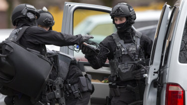 Counter terrorism police prepare to enter a house after the shooting incident.