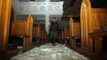 A man walks inside a church where debris has fallen after the earthquake in Bali.