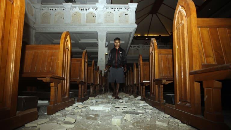A man walks inside a church where debris has fallen after the earthquake in Bali.