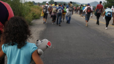 A girl carries a stuffed teddy bear as she walks with her mother with a migrant caravan near Arriaga, Chiapas state, Mexico, on  October 27.