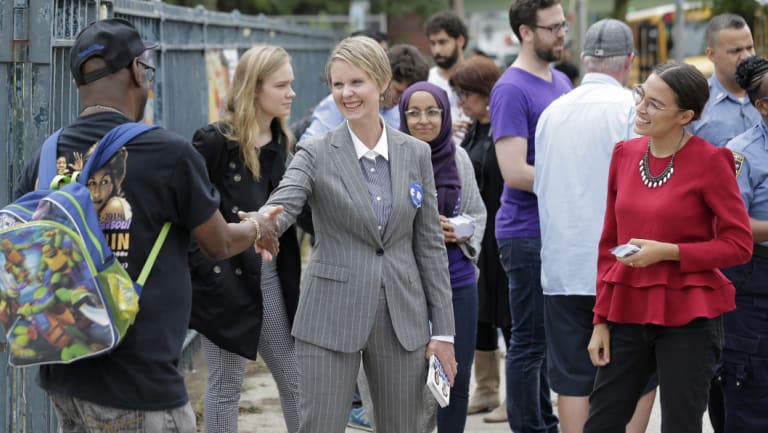 Democratic gubernatorial candidate Cynthia Nixon, centre, and congressional candidate Alexandria Ocasio-Cortez, right, greet voters and children outside a school while campaigning in New York.