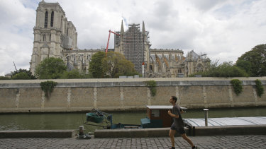 A man jogs along the Seine River near Notre-Dame.