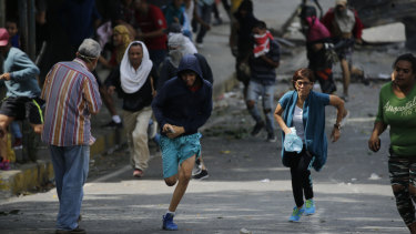 Anti-government protesters run during clashes with security forces as they show support for an apparent mutiny by a Venezuelan National Guard unit.