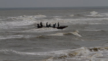 Indian fishermen attempt to bring their boat ashore amid strong winds at Chandrabhaga beach in the Puri district of eastern Odisha state, India.