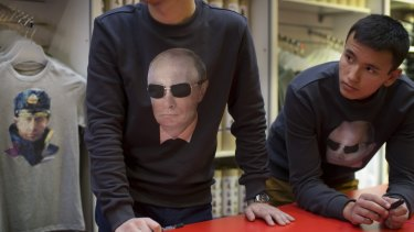 Putin, pictured on souvenir t-shirts, is the country's brand, analysts say.