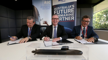 Naval Group Australia CEO John Davies, Minister for Defence Christopher Pyne and ASC CEO Stuart Whiley sign a working agreement for Australia's future submarines project.