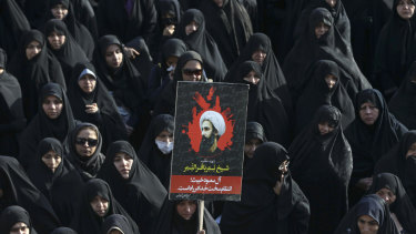 An Iranian woman holds up a poster showing Sheikh Nimr al-Nimr, a prominent opposition Saudi Shiite cleric who was executed by Saudi Arabia, in Tehran, Iran, in 2016.