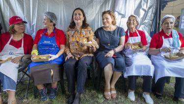 Queensland Premier Annastacia Palaszczuk (centre) and Queensland Deputy Premier Jackie Trad are seen sitting with cooks at the Greek Paniyiri Festival in Brisbane.