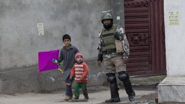 Kashmiri children walk past an Indian paramilitary soldier in Srinagar, Indian-controlled Kashmir.