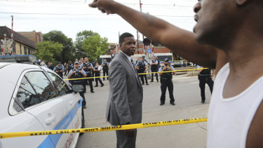 Members of the Chicago Police Department look at an angry crowd gathered at the scene of a police involved shooting in Chicago, on Saturday.