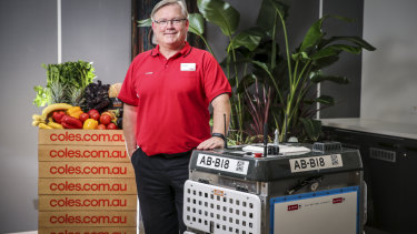 Coles chief Steven Cain with one of the 'daleks' that will pick online grocery orders.