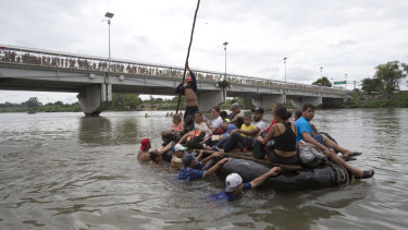 A group of Central American migrants cross the Suchiate River on the the border between Guatemala and Mexico, in Ciudad Hidalgo. Others attempted to swim across.