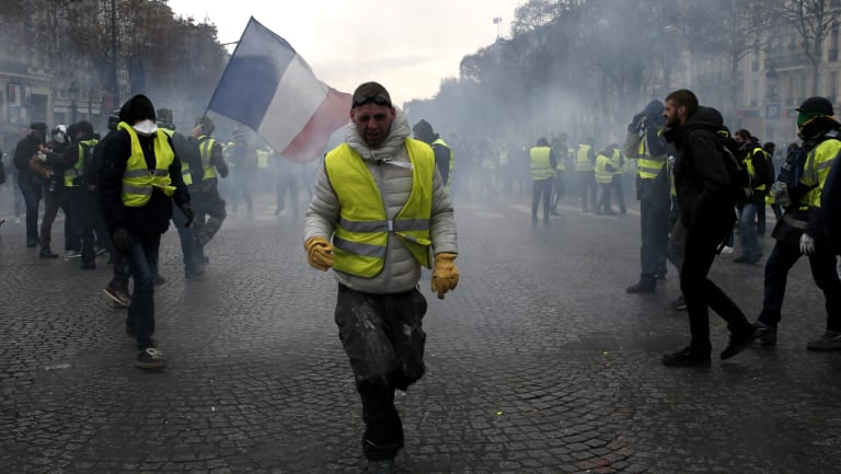 A demonstrator wearing a yellow vest grimaces through tear gas.
