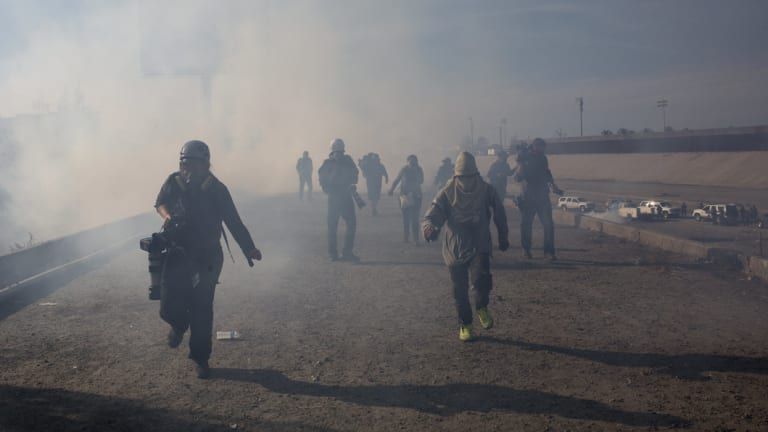 Migrants and journalists run from tear gas launched by US agents at the Mexico-US border.