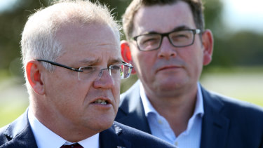Prime Minister Scott Morrison speaks to the media while Victorian Premier Daniel Andrews looks on .