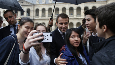 France's President Emmanuel Macron, centre, poses with students after a military ceremony at the Hotel des Invalides, in Paris.