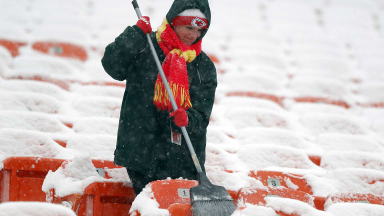 A groundskeeper brushes snow off seats at Arrowhead Stadium before an NFL divisional football playoff game  in Kansas City on  Saturday.