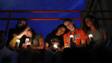 From left, Melody Stout, Hannah Payan, Aaliyah Alba, Sherie Gramlich and Laura Barrios comfort each other during a vigil for victims of the shooting on Saturday.