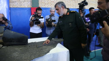 Head of the Revolutionary Guard's aerospace division General Amir Ali Hajizadeh points at the wreckage of US drone RQ-4A in Tehran.
