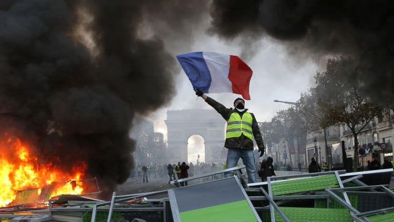 A demonstrator waves the French flag on a burning barricade on the Champs-Elysees