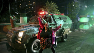 A woman shouts in front of a police truck near the Santa Lucia subway station during a protest against the rising cost of subway and bus fares, in Santiago.