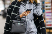 PARIS, FRANCE - FEBRUARY 28: A guest wears a black and white checked pattern plaid long coat, a Hermes bag, a denim jumpsuit, a turtleneck top, outside Ralph & Russo, during Paris Fashion Week - Womenswear Fall/Winter 2020/2021, on February 28, 2020 in Paris, France. (Photo by Edward Berthelot/Getty Images) Get the look: back to the office