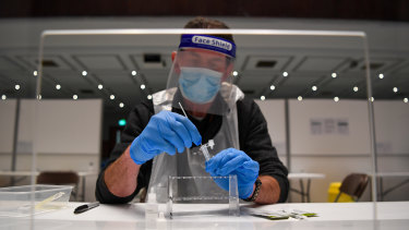 A worker tests a sample for COVID-19 in Portsmouth, England.