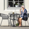 People sit in the sun outside a cafe in Wellington on Sunday. NZ is on level-two alert, while Auckland is in lockdown because of new cases.
