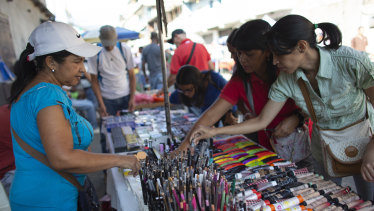 Daixy Aguero, left, sells makeup at a market in Caracas, Venezuela.