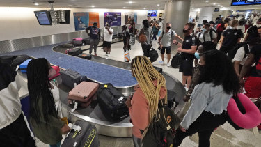 Life returning to normal: travellers wait for their luggage at a baggage carousel at Miami International Airport.