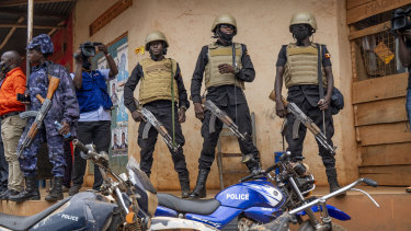 Security forces stand outside a polling station in Kampala on Thursday.
