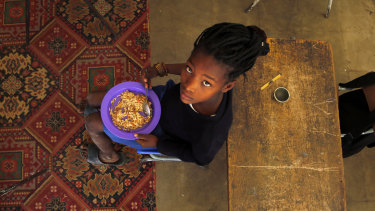A child eats a meal received from a government sponsored feeding scheme at the Delta Primary School in Vosburg, South Africa.