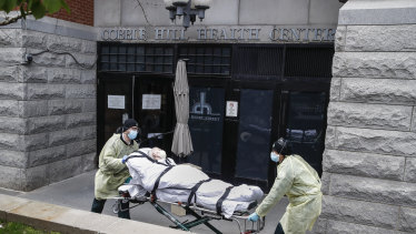A patient is wheeled out of the Cobble Hill Health Centre by emergency medical workers in the Brooklyn borough of New York.