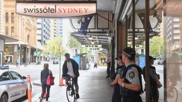 Police guard the Swissotel on Market Street in Sydney, which is being used to quarantine Australians returning to the country by plane.