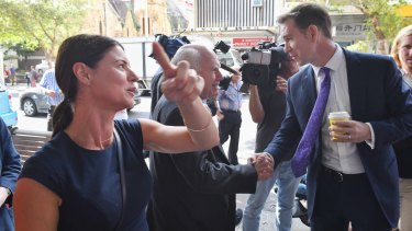 Labor candidate Sam Crosby jumps in and shakes hands with John Howard in Burwood.