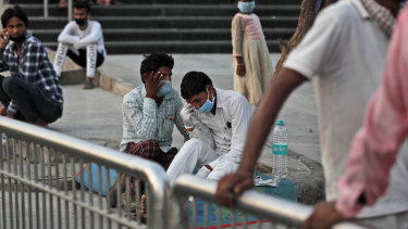 Relatives of admitted patients wearing face masks as a precaution against coronavirus talk outside a hospital in New Delhi earlier this month.