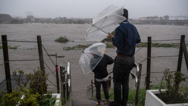 People look at the flooded Tama River during Typhoon Hagibis on October 12.