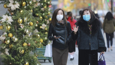 Shoppers wear face masks to help curb the spread of the coronavirus in the Ginza shopping district in Tokyo today.