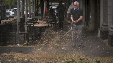 University Cafe owner Giancarlo Capriol cleaning up his shop front on Lygon Street after the storm.