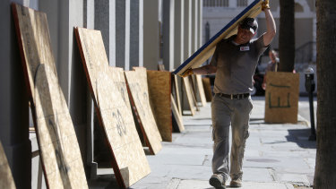Preston Guiher carries a sheet of plywood as he prepares to board up a Wells Fargo bank location in preparation for Hurricane Florence in downtown Charleston, SC.